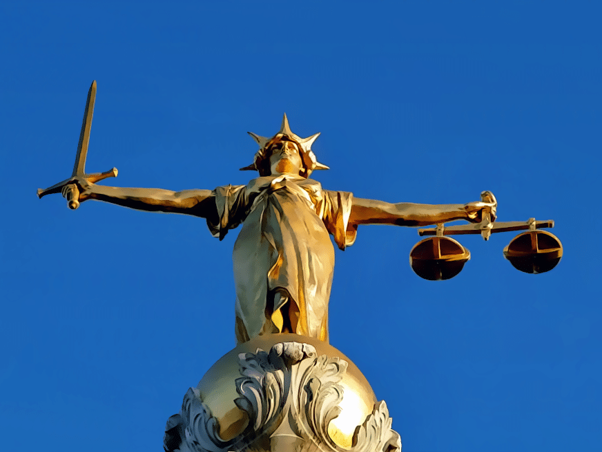 A statue of Lady Justice, the personification of the moral force in judicial systems, holding a sword and scales.