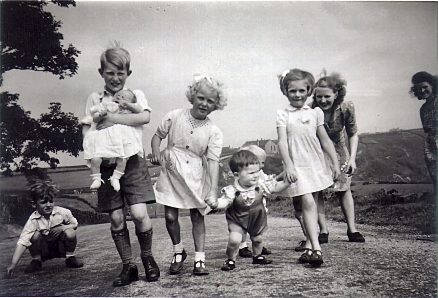 Photo of 1 year old Norky holding his sister Rhondda's hand, together with other children (1948)