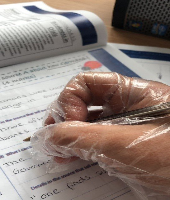 Photo of a teacher's hand marking homework with a plastic glove on to avoid catching or spreading the coronavirus