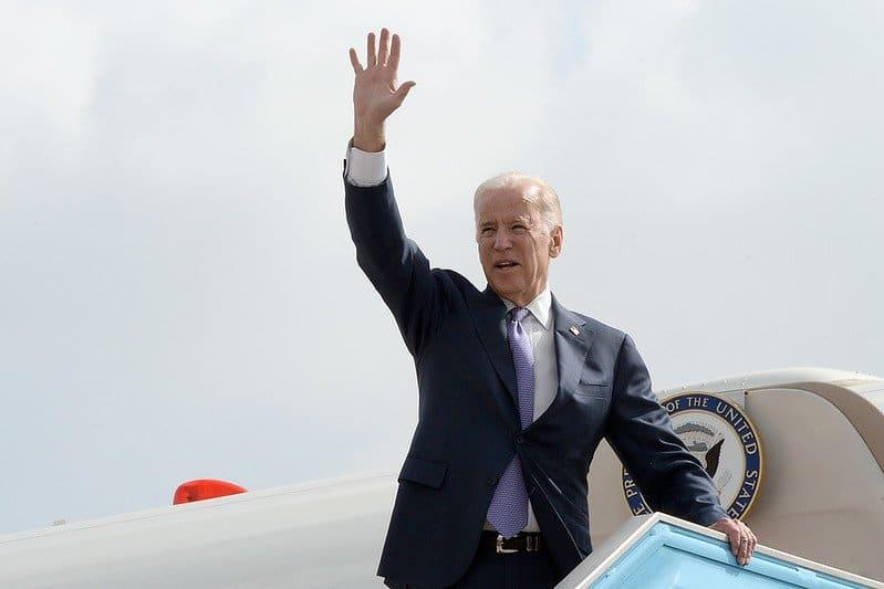 Joe Biden waving as he prepares to board a plane.