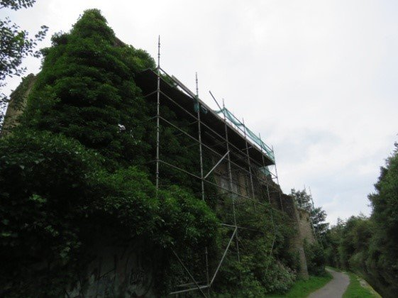 A disused mill covered in scaffolding.