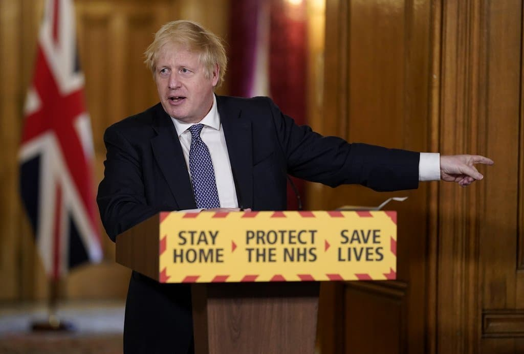 Image description: Boris Johnson speaking during a coronavirus briefing, gesturing towards a graph