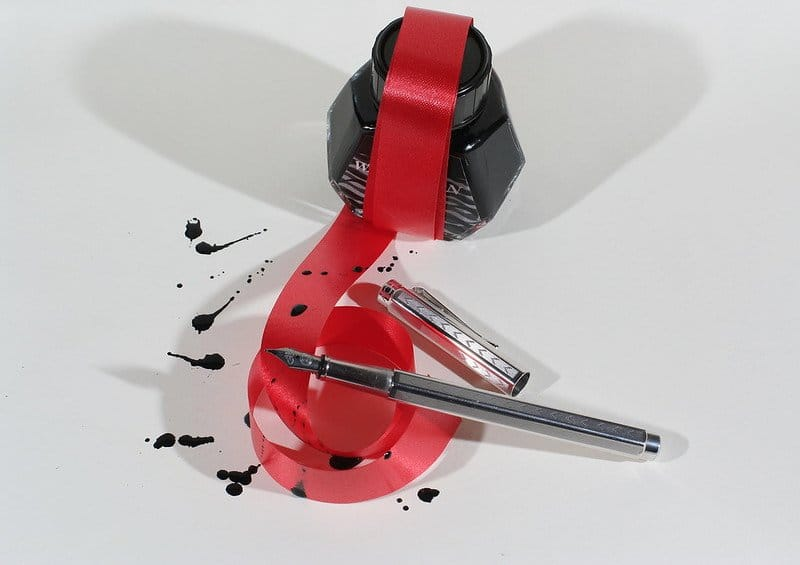 Image of an inkpot and fountain pen tied up in red tape
