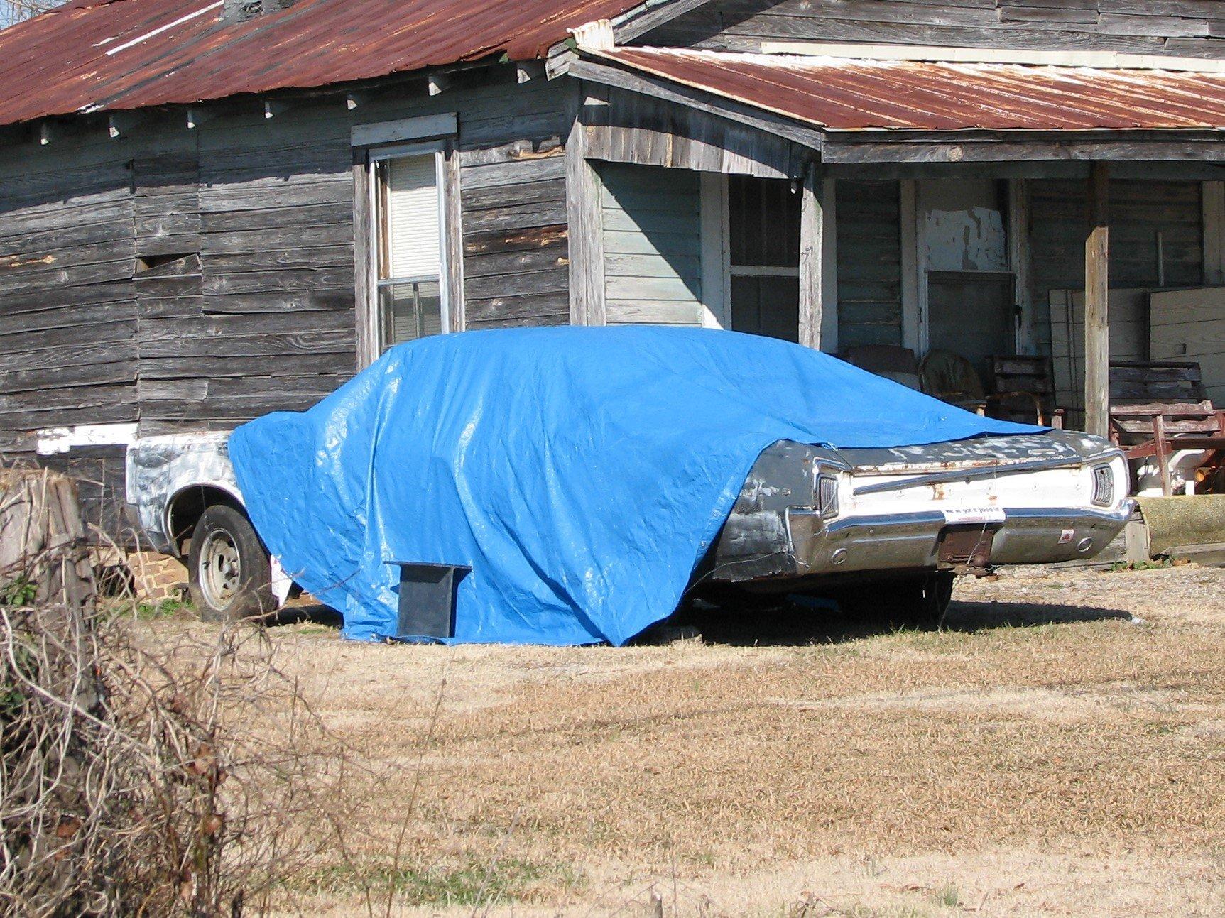 Image of a car under a blue tarpaulin