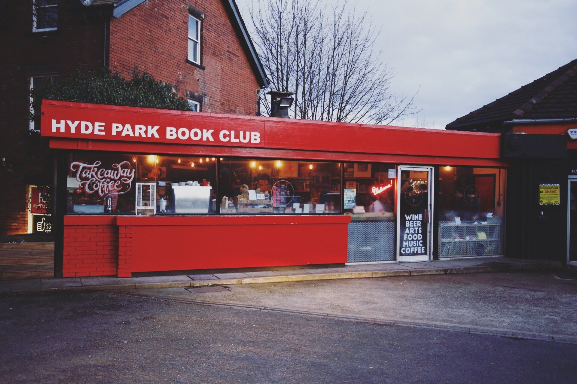 """Image description: A red-fronted cafe with a long front window. Neon light emanates from the inside, and the windows are full of coffee machines, baked goods and signs. A sign on the top left reads """"Hyde Park Book Club"""", the glass door advertises """"Wine, Beer, Arts, Food, Music, Coffee"""""""