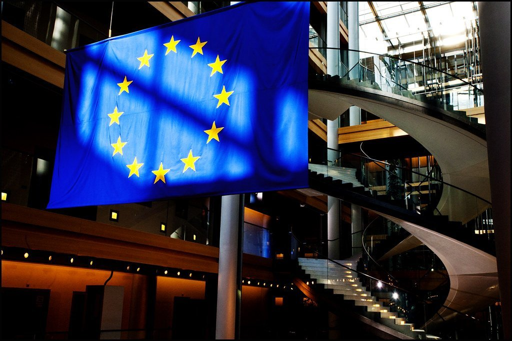 Image description: An EU flag illuminated by natural light in the European Parliament at Strasbourg.