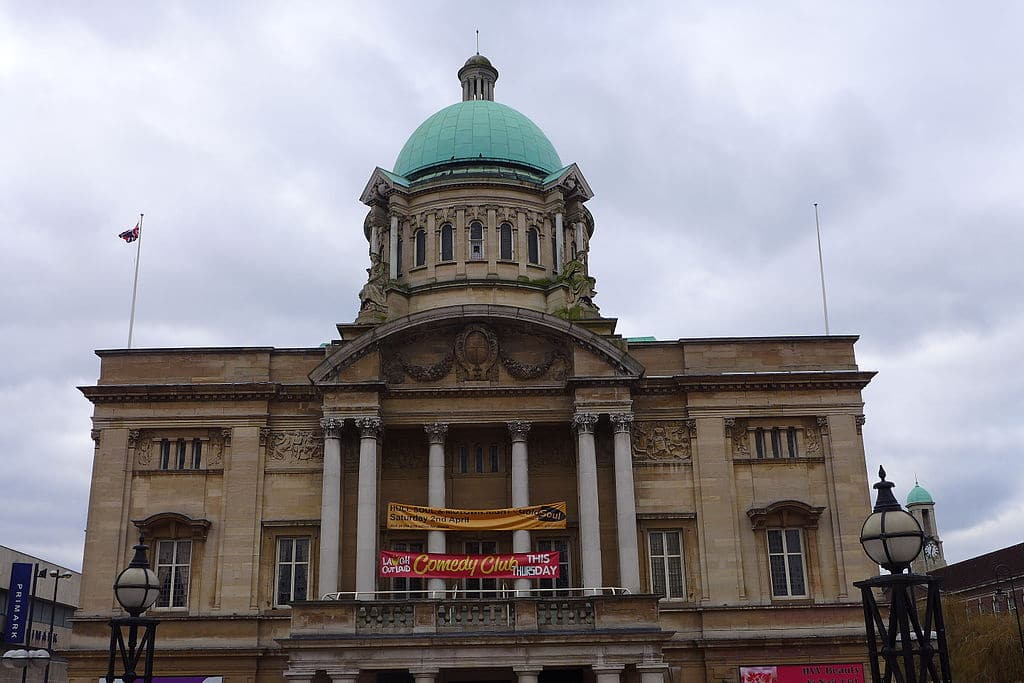 Image description: Hull City Hall, a typical neoclassical building with a sandstone facade, a set of columns and a rusted copper dome.
