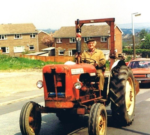 Image description: Peter Norcliffe's uncle Harold in a red tractor, driving through Huddersfield.