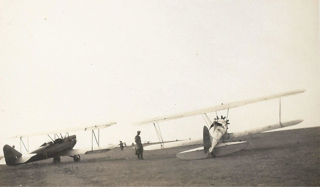 Image description: A black and white image of two biplanes on the ground. A man stands between the two, too small to see what he's doing.