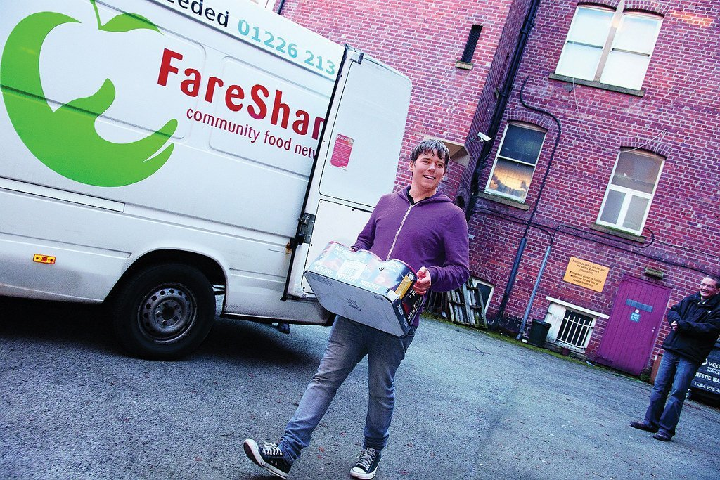 Image description: a volunteer carrying large cans of chopped tomatoes, a Barnsley FareShare van in the background