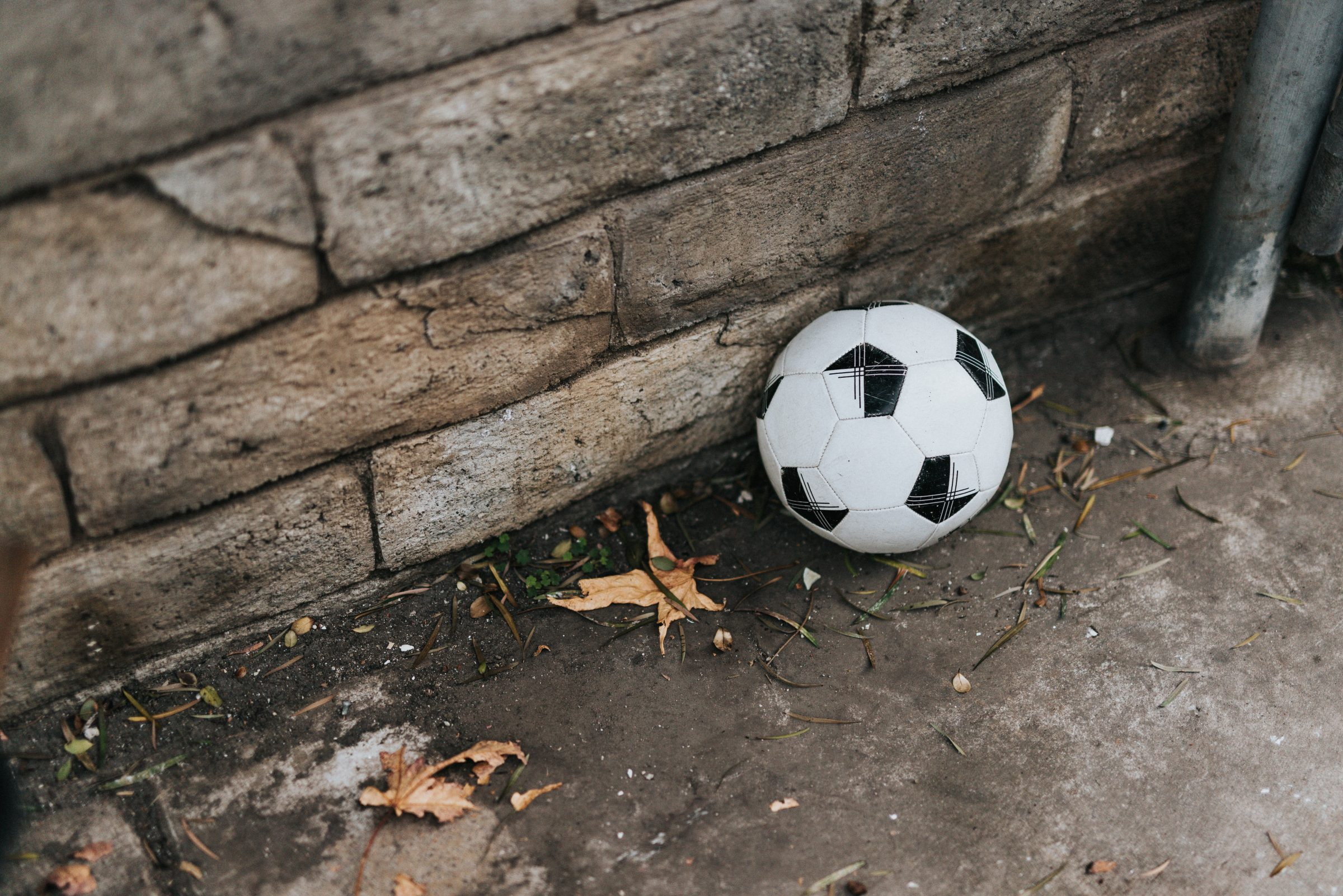 Image of a football on the ground by a wall with some leaves