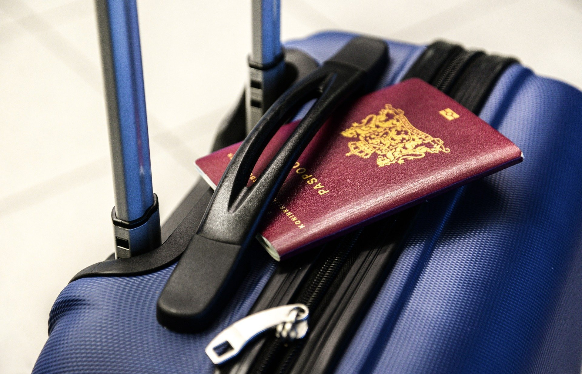 Image description: burgundy passport wedged into the handle of a blue suitcase.