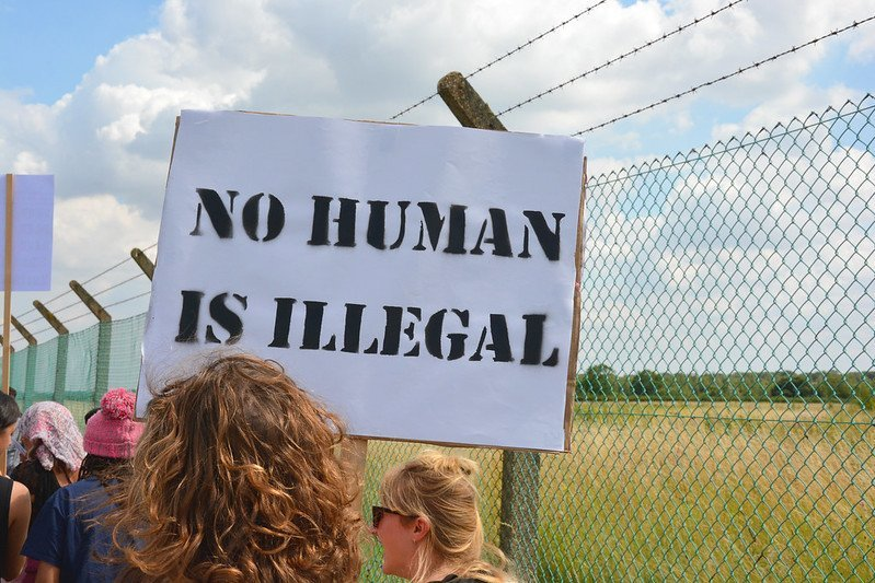 """Photo of protest at Yarl's Wood - placard says """"No human is illegal"""""""