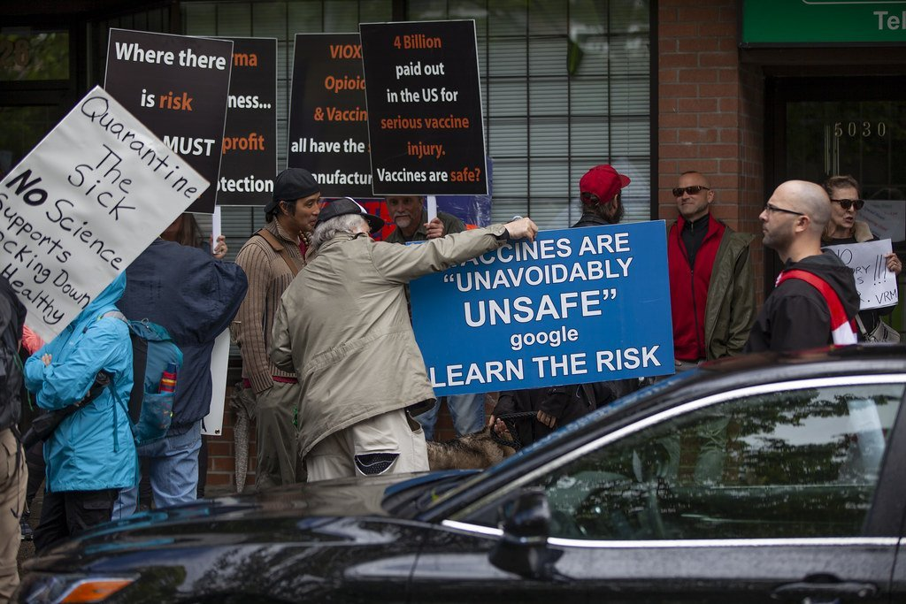 "Image description: anti-lockdown protesters in Canada, holding up conspiracy-supporting signs like ""Vaccines are ""unavoidably unsafe"" google learn the risk"" and ""Quarantine the sick No Science supports locking down the healthy"""