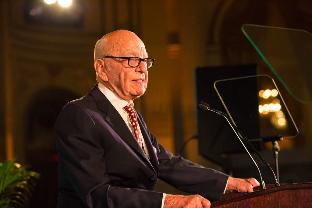 Image description: Rupert Murdoch speaking at a podium in front of teleprompters.