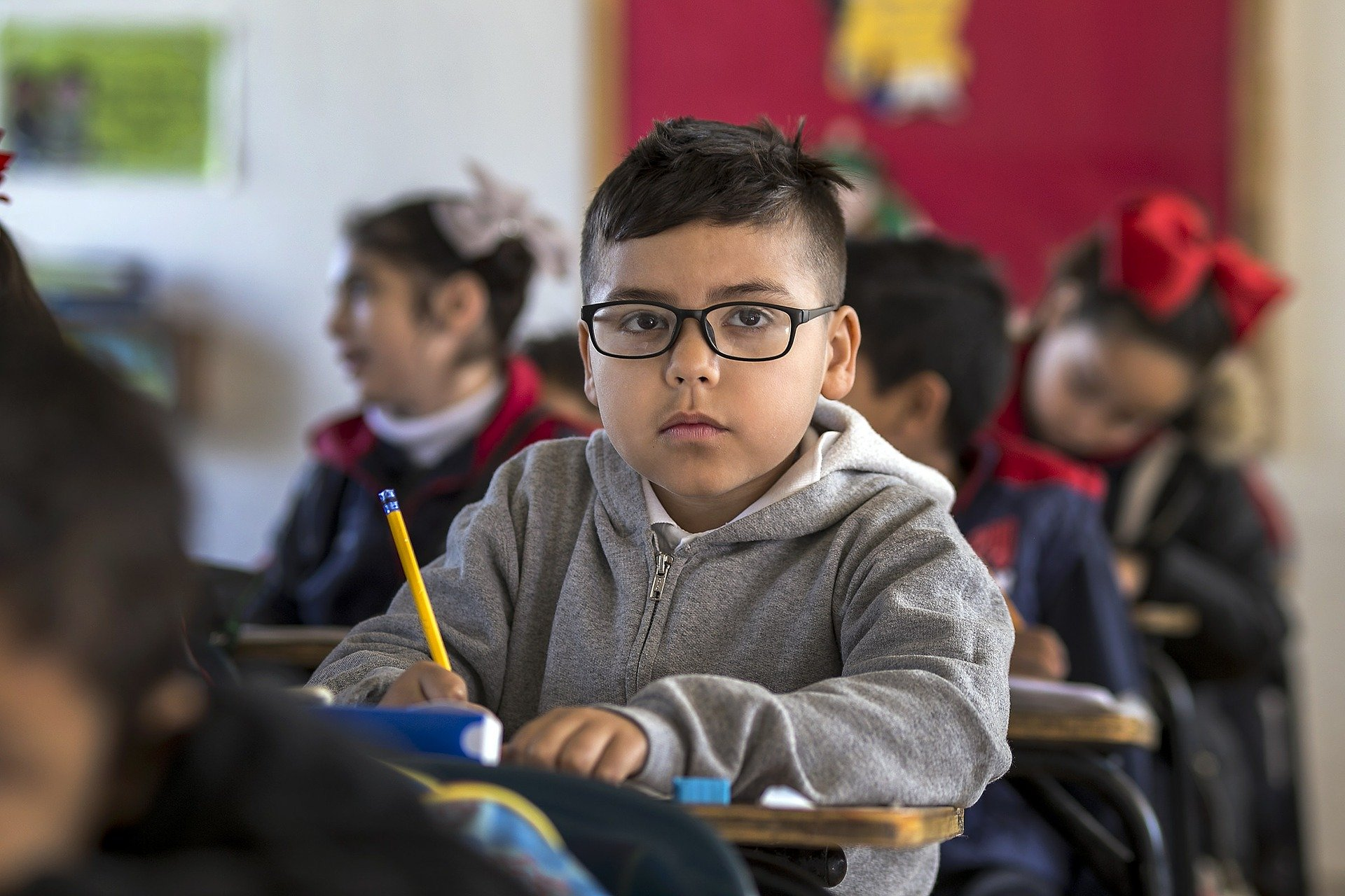 Image description: a young child with glasses at a desk in a classroom, pencil in hand.